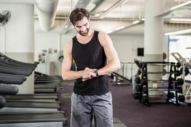 Sorrindo, homem, ligado, treadmill, olhar, smartwatch, em, a, ginásio