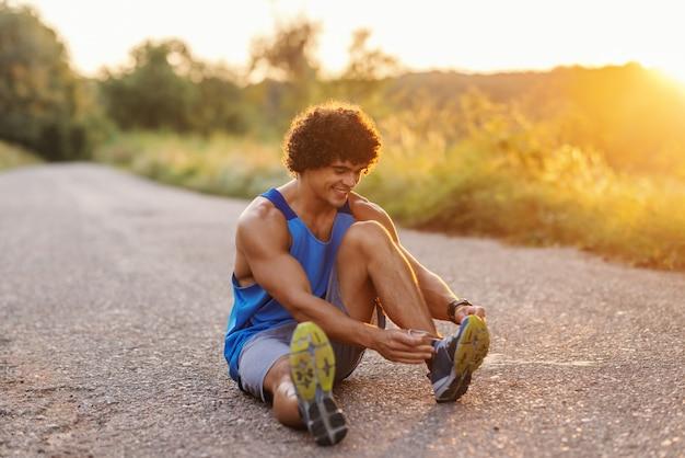 Sorrindo homem musculoso com cabelos cacheados, sentado na estrada e amarrar o cadarço. dia ensolarado de verão.