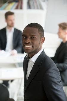 Sorrindo, homem negócios africano, desgastar, paleto, headshot, vertical, retrato, com, equipe