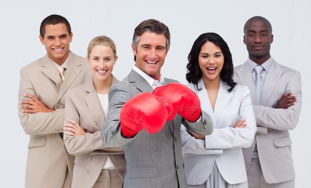 Sorrindo, homem negócios, com, luvas boxing, guiando, seu, equipe