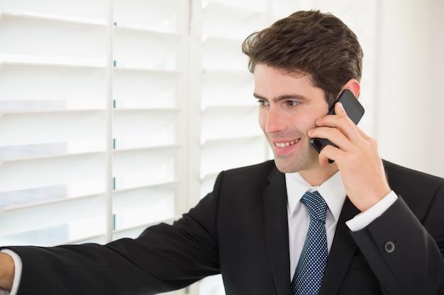 Sorrindo, homem negócios, espreitar, através, cortinas, enquanto, ligado, chamada