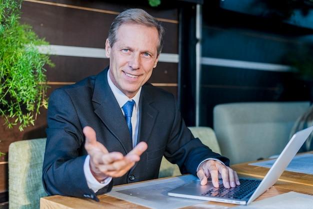 Sorrindo, homem negócios, fazer, gesto mão, com, laptop, escrivaninha, em, restaurante