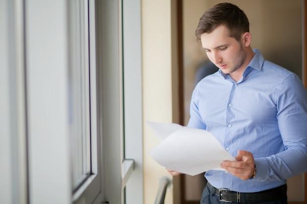 Sorrindo, homem negócios fica, pela janela, em, escritório, e, leitura, papel