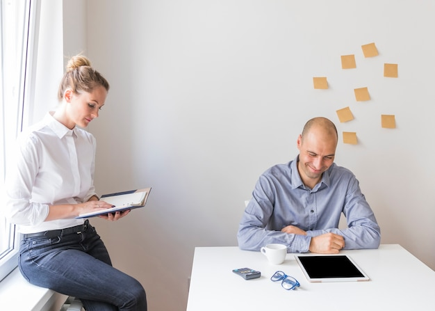 Sorrindo, homem negócios, olhar, tablete digital, com, executiva, olhar, diary, em, escritório