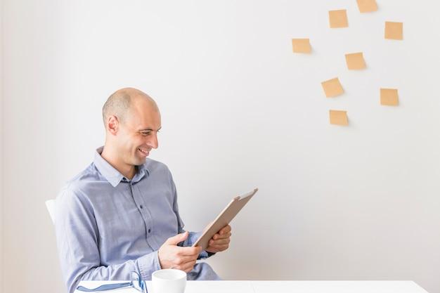Sorrindo, homem negócios, olhar, tablete digital, sentando, frente, parede, com, notas pegajosas