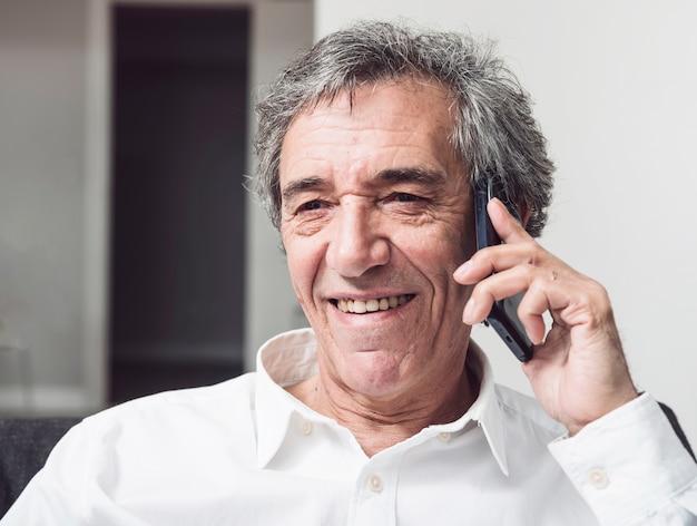 Sorrindo, homem negócios sênior, conversa num smartphone