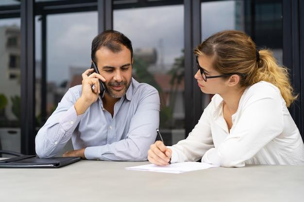 Sorrindo, homem negócios, sentando, em, reunião, em, falando telefone