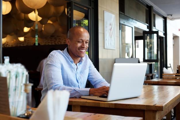Sorrindo, homem negócios, sentando, tabela, com, laptop