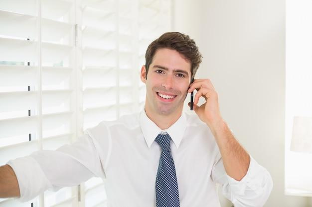 Sorrindo, homem negócios, usando, móvel, telefone, escritório