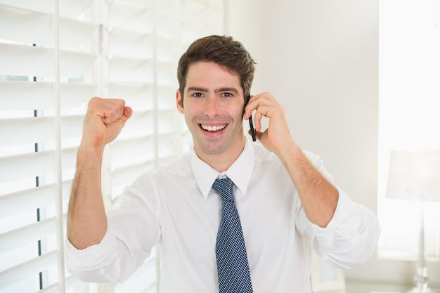 Sorrindo, homem negócios, usando, telefone móvel, enquanto, clenching, punho