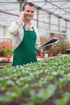 Sorrindo homem no telefone e tomando notas em casa de vegetação