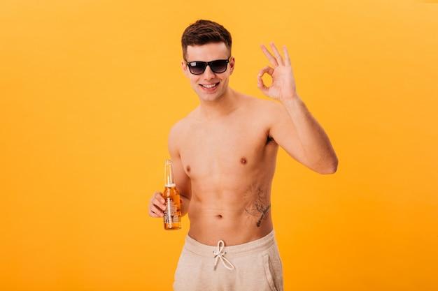 Sorrindo homem nu de bermuda e óculos escuros, segurando a garrafa de cerveja e mostrando bem assinar sobre amarelo