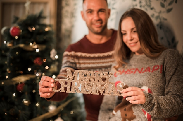 Sorrindo, homem, perto, alegre, mulher, com, feliz natal, tabuleta, perto, decorado, árvore abeto