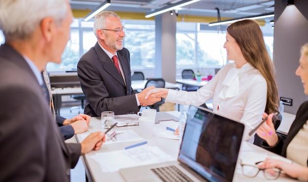 Sorrindo, homem sênior, apertar mão, com, jovem, executiva, em, escritório