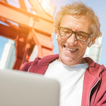 Sorrindo, homem sênior, óculos desgastando, usando computador portátil