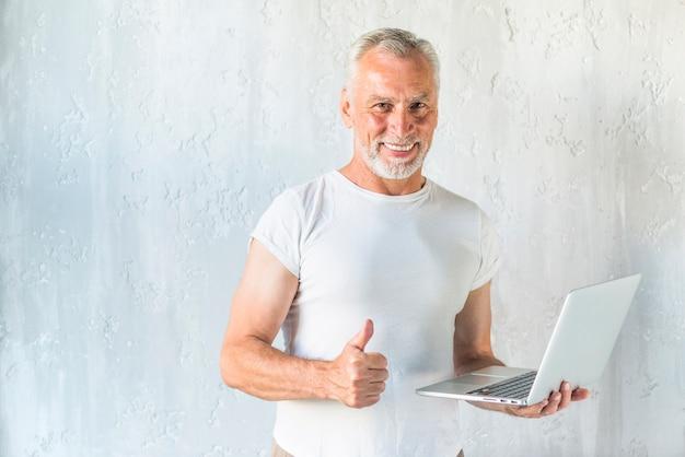 Sorrindo, homem sênior, segurando, laptop, mostrando, polegar cima, sinal