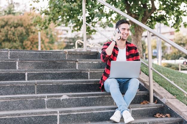 Sorrindo, homem sentando, ligado, escadaria, falando, ligado, smartphone