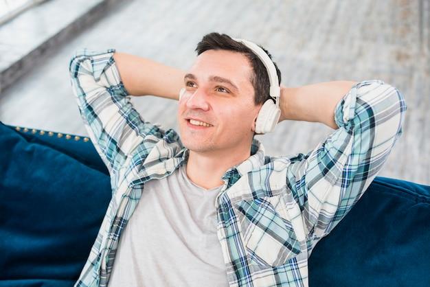 Sorrindo homem sonhador escuta música em fones de ouvido no sofá
