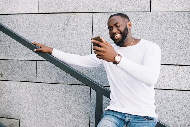Sorrindo, homem, usando, smartphone, escada
