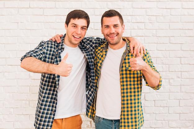 Sorrindo, homens jovens, com, seu, braços ao redor, seu, ombro, mostrando, polegar cima, sinal