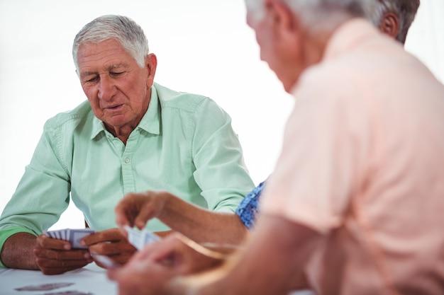 Sorrindo idosos pessoas jogando cartas
