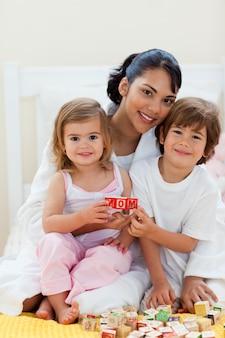 Sorrindo irmãos e sua mãe brincando com blocos de letras