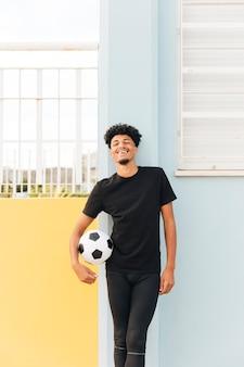 Sorrindo, jogador de futebol, segurando bola, e, olhando câmera