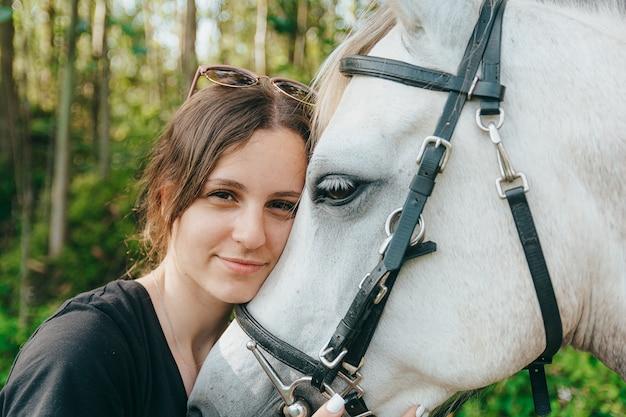 Sorrindo jovem abraçando carinhosamente seu cavalo castanho depois de dar um passeio