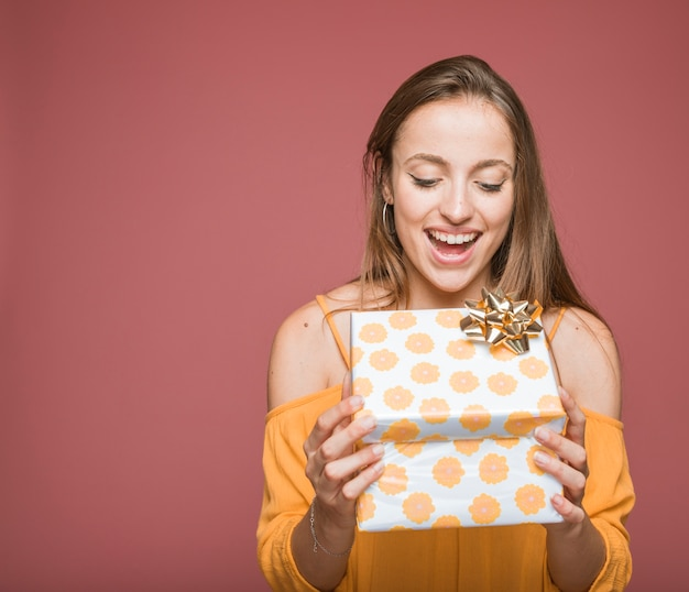 Sorrindo jovem abrindo a caixa de presente floral com laço dourado