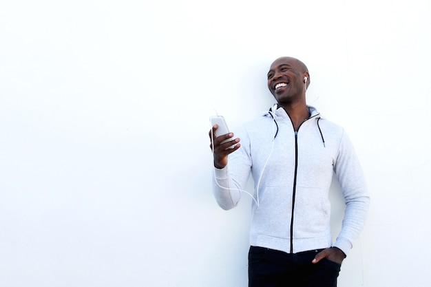 Sorrindo, jovem, africano, homem, com, telefone móvel, e, fones