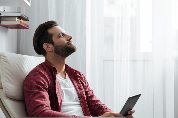 Sorrindo jovem barbudo usando computador tablet.