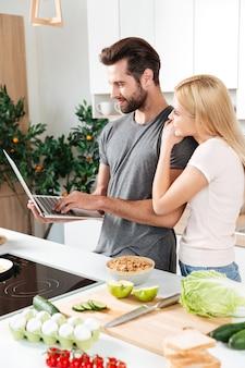 Sorrindo jovem casal apaixonado, cozinhando juntos usando laptop