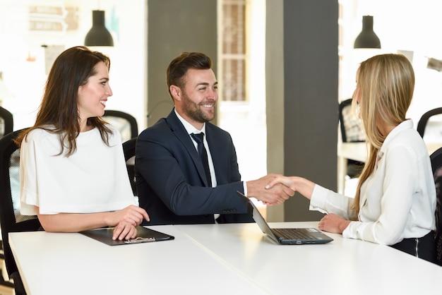 Sorrindo jovem casal apertando a mão com um agente de seguros