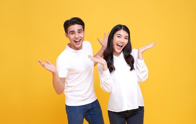 Sorrindo jovem casal asiático homem e mulher feliz e espantado com fundo amarelo.