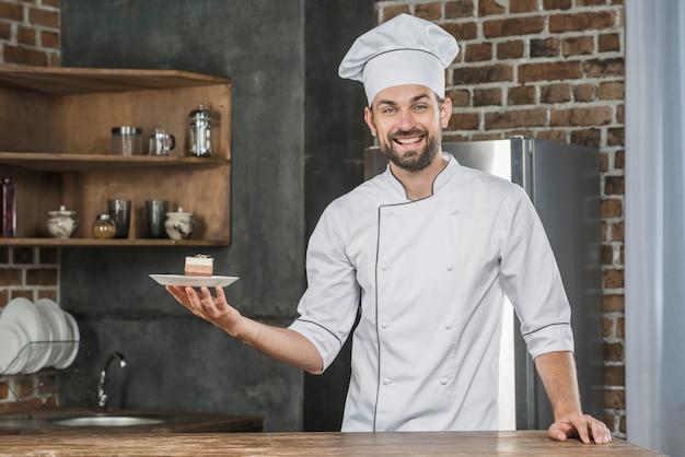 Sorrindo jovem chef masculino apresentando sobremesa na cozinha