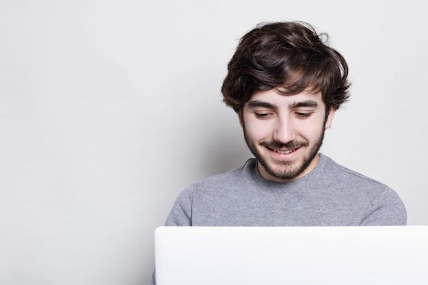 Sorrindo jovem com barba na moda e penteado fazendo videochamada