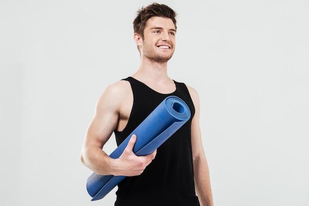 Sorrindo jovem desportista segurando o tapete de fitness