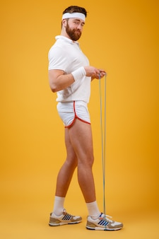 Sorrindo jovem desportista segurando pular corda