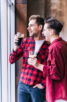 Sorrindo jovem dois amigo masculino segurando os copos de cerveja