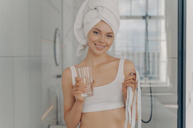 Sorrindo, jovem e atraente mulher caucasiana com um copo d'água em uma mão e uma fita métrica na outra, de pé no banheiro após o banho matinal, usa cueca branca. conceito de emagrecimento