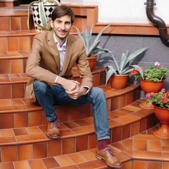 Sorrindo jovem elegante sentado ao ar livre nas escadas circulares vintage
