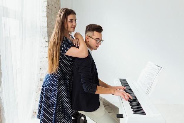 Sorrindo jovem em pé atrás do homem tocando piano