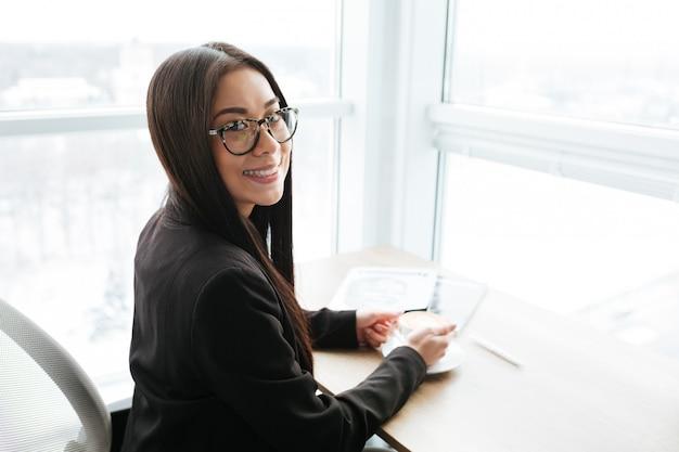 Sorrindo jovem empresária asiática sentado e tomando café no escritório