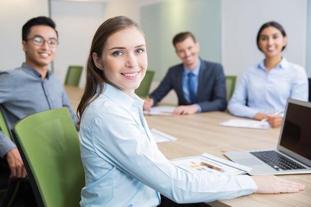 Sorrindo jovem empresária sentado na sala de reuniões