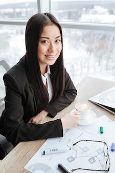 Sorrindo jovem empresária tomando café na mesa no escritório