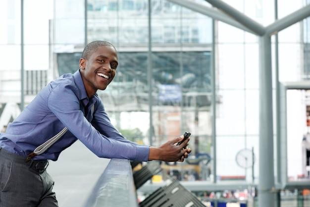 Sorrindo jovem empresário preto com celular