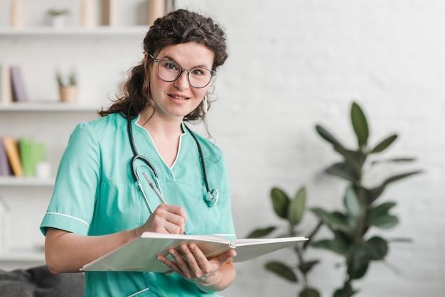 Sorrindo jovem enfermeira com livro e caneta na clínica
