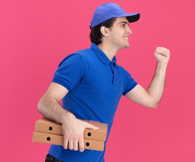 Sorrindo, jovem entregador caucasiano de uniforme azul e boné em pé na vista de perfil, segurando pacotes de pizza, fazendo gesto de bater, olhando diretamente isolado na parede rosa