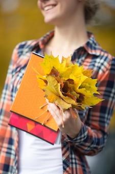 Sorrindo jovem estudante atraente ao ar livre segurando folhas amarelas