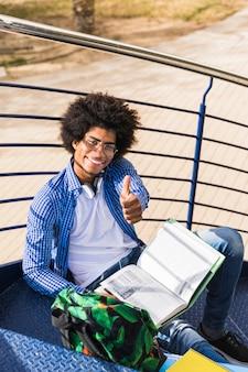 Sorrindo, jovem, estudante masculino, sentando, ligado, escadaria, mostrando, polegar cima, sinal